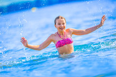 Cute young girl playing in the sea.  Happy pre-teen girl enjoys summer water and holidays in holiday destinations.  Royalty Free Stock Photography