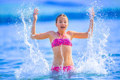 Cute young girl playing in the sea.  Happy pre-teen girl enjoys summer water and holidays in holiday destinations Stock Photography