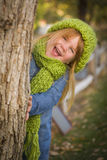 Cute Young Girl Plays Peek-a-boo Wearing Green Scarf And Hat Stock Photography