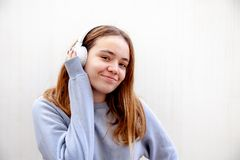 Teenage girl plays with wireless headphones on a white background royalty free stock image