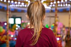Girl with a ponytail looking at a carousel royalty free stock images