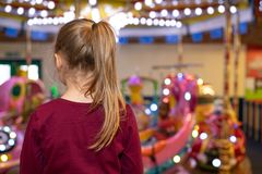 Girl with a ponytail looking at a carousel stock photo