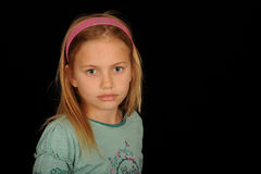 Cute young girl portrait. Half body portrait of young girl wearing headband, isolated on black background Royalty Free Stock Photo