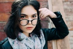 Beautiful happy hipster girl goes in the city. Closeup of trendy girl face. Stock Photos