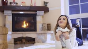 Cute young girl posing for camera laying near the fireplace stock video