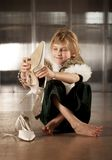 Cute young girl putting on adult shoe Royalty Free Stock Images