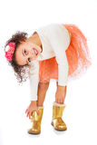 Cute young girl putting on boots. A pretty young African American girl putting on her gold boots Royalty Free Stock Photos