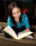 Cute young girl reading  a big book. Royalty Free Stock Photography