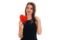 Cute young girl with red lipstick and black dress looks straight smiles and holds Valentine Stock Photos