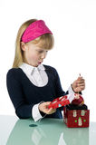 Cute young girl removing a Christmas ornament Stock Photos