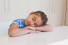 Cute young girl resting head on table Stock Image