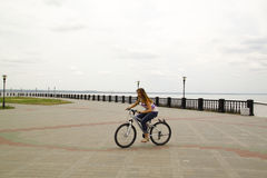 Cute young girl rides a bicycle Stock Image