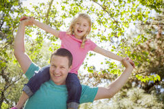 Cute Young Girl Rides Piggyback On Her Dads Shoulders. Outside at the Park royalty free stock photography