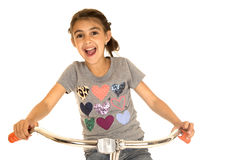 Cute young girl riding a bicycle with a happy facial expression Royalty Free Stock Images