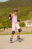 Cute young girl rollerskates Stock Image