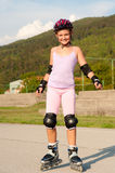 Cute young girl rollerskates Stock Photo