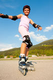 Cute young girl rollerskates on a playground Stock Photos