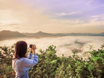 Cute young girl 25s to 35s with her camera enjoy see and take. Picture to haze around mountain with sunrise and nice sky from north east thailand Royalty Free Stock Photo
