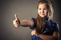 Cute young girl showing thumbs up stock photos