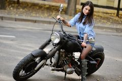 Cute young girl sitting on a big motorcycle. On the background of trees Stock Photo