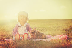 Cute young girl sitting on blanket and cuddles a rabbit Stock Photography