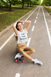 Cute young girl sitting on a longboard, crossed her arms over her head on the road in the park. Skateboarding. Outdoors Stock Photos