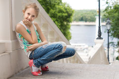 Cute young girl sitting on an outdoor staircase Stock Photography