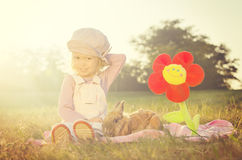 Cute young girl sitting beside a rabbit and flower Royalty Free Stock Image
