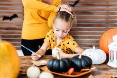 Cute young girl sitting at a table, decorating little white pumpkins. DIY Halloween concept. Cute young girl sitting at a table, decorating little white royalty free stock photography