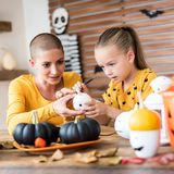 Cute young girl sitting at a table, decorating little white pumpkins with her mother, a cancer patient. DIY Halloween. Cute young girl sitting at a table stock photography
