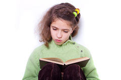 Cute young girl sitting by the wall and reading a Royalty Free Stock Photos