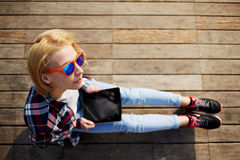 Cute young girl spends time on the pier and checks mail photographed Royalty Free Stock Image