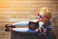 Cute young girl spends time on the pier and checks mail photographed Royalty Free Stock Photo