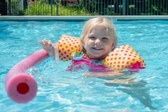 Cute young girl splashing in the pool on a summer day. Cute young girl splashing in the swimming pool on a summer day - childhood fun, summer vacation royalty free stock photos