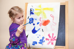 Cute young girl standing with painting brush Royalty Free Stock Photo