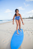 Cute young girl standing on surfboard Royalty Free Stock Image