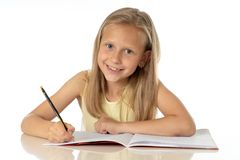 Cute young girl studying at home on a desk with a study book on a white background stock photos