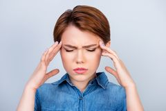 Cute young girl is suffering from strong headache. She is holding her head with hands stock photos