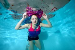 Cute young girl swims underwater in the pool on a blue background with a big red bow on her head and looking at the camera. Portra. It. Horizontal orientation. A Stock Image