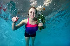 Cute young girl swims underwater in the pool on a blue background with a Christmas tree with a toy in hand. Looking at camera and smiling. Portrait. Horizontal Royalty Free Stock Photography