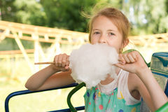 Cute young girl tucking into a ball of candy floss Royalty Free Stock Photography