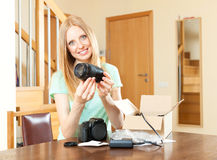 Cute young  girl unpacking new digital camera  in home interior Stock Photography