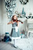 Cute young girl with violinl in christmas decoration room. Young girl playing violin at Christmas tree. Toned photo Royalty Free Stock Photography