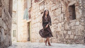 Cute young girl walking in the old town. Nice female child in medieval city. Stock Photos