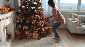 Cute young girl walking to a Christmas tree takes a gift and walks away. At home stock footage