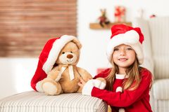 Cute young girl wearing santa hat holding her christmas present, soft toy teddy bear. Happy kid with xmas present. Cute young girl wearing santa hat holding her royalty free stock images