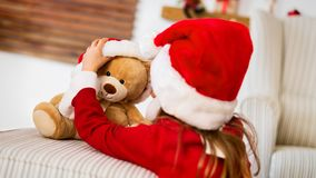 Cute young girl wearing santa hat playing with her christmas present, soft toy teddy bear. Happy kid with xmas present. Cute young girl wearing santa hat stock image