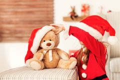 Cute young girl wearing santa hat playing with her christmas present, soft toy teddy bear. Happy kid. Cute young girl wearing santa hat playing with her royalty free stock photos