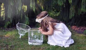 Cute young girl wearing a spring dress and a wreath of flowers swinging on a swing Royalty Free Stock Photography