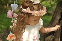 Cute young girl wearing a spring dress and a wreath of flowers swinging Royalty Free Stock Photography